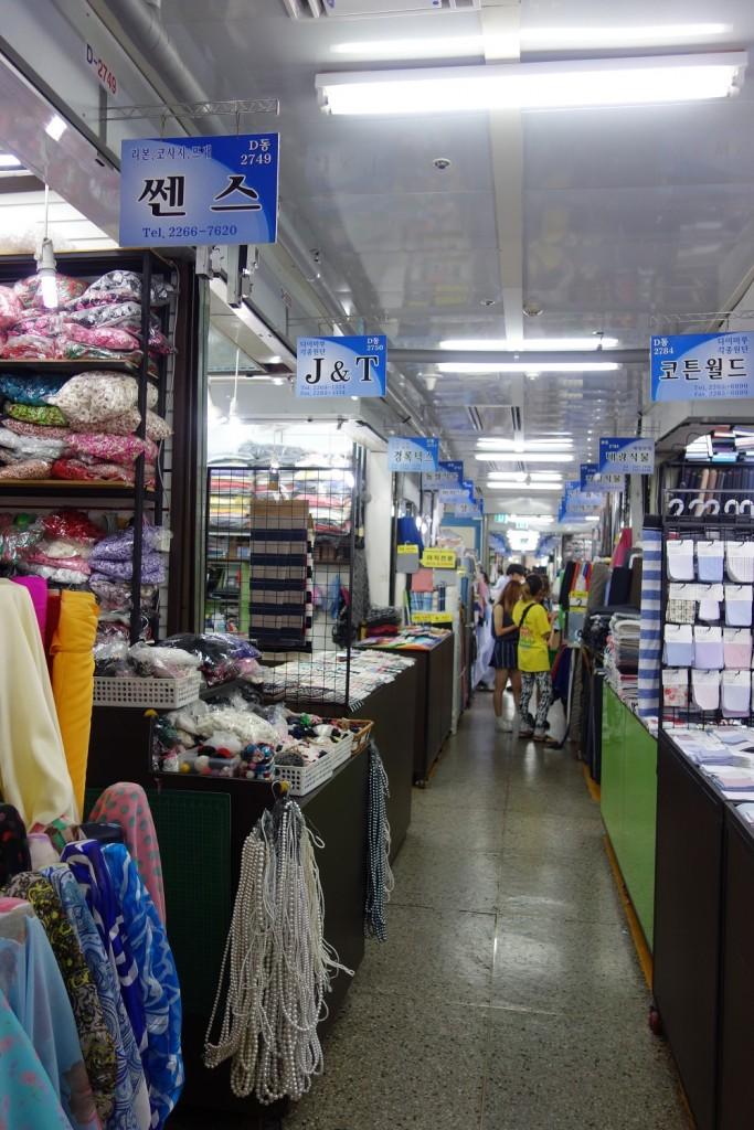langer Gang mit Verkaufsständen für Stoffe und Zubehör