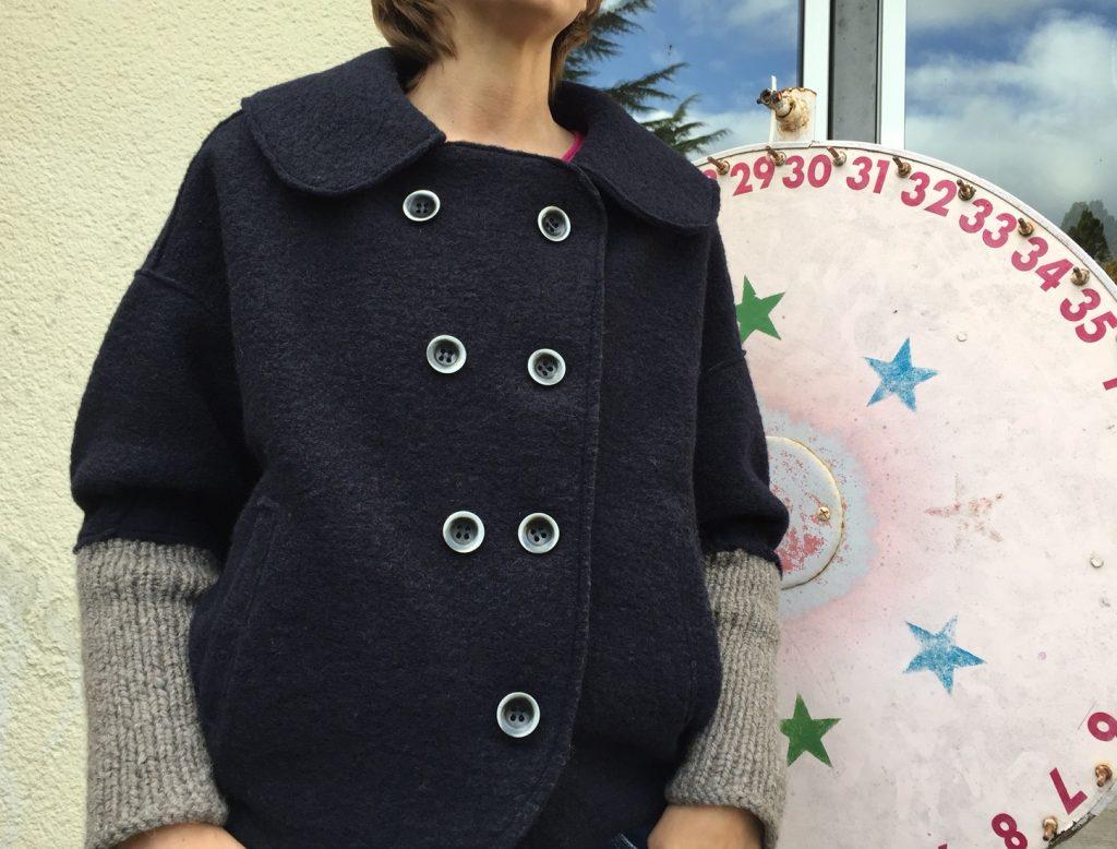 genähte dunkelblaue Winterjacke vor einem Glücksrad