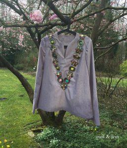 Tunika hängt am Bügel im Kirschbaum