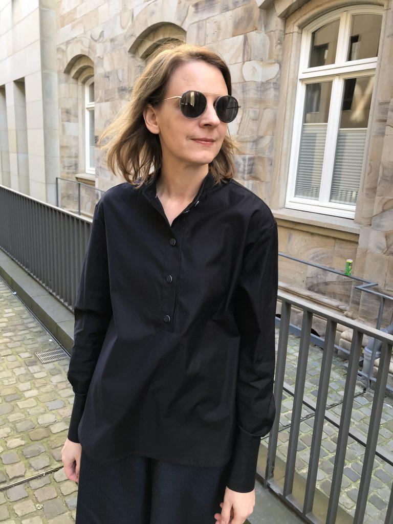 dunkelblaue Bluse mit offen getragener Knopfleiste